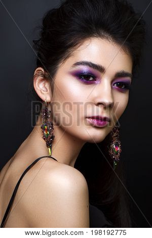 Portrait of beautiful young woman with professional makeup, perfect skin, big earrings Trendy lilac smoky eyes.