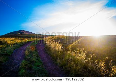 Road through the hill to the top. mountain ridge is seen in the distance. Evening sun colors dry grass in gold