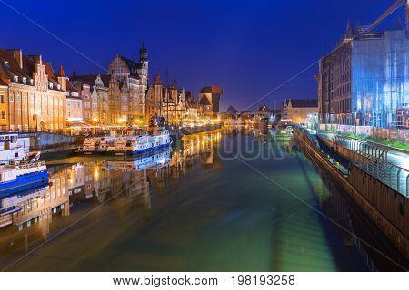 GDANSK, POLAND - JULY 27, 2017: Historic port crane over Motlawa river in Gdansk at night, Poland. Gdansk is the historical capital of Polish Pomerania.