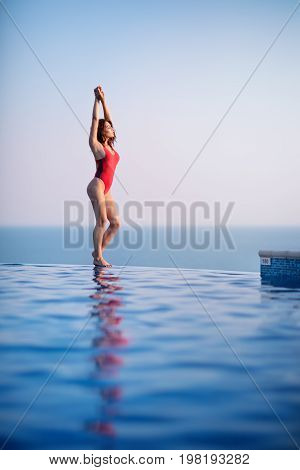 Beautiful young woman in swimsuit at the edge of infinity swimming pool