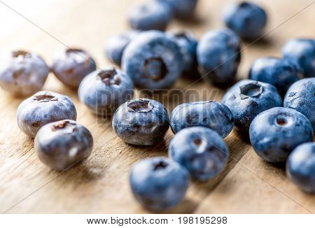 Freshly blueberries on wooden rustic wooden table. Juicy and fresh blueberries with green leaves. Bilberry on wooden background. Blueberry antioxidant. Concept for healthy eating and nutrition.