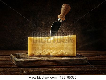 Parmesan cheese on rustic wooden board. Pieces of cheese parmesan on wooden table with cheese knife.
