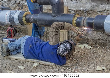 Welder Welding Underground Steel Pipe Lying On Ground 2