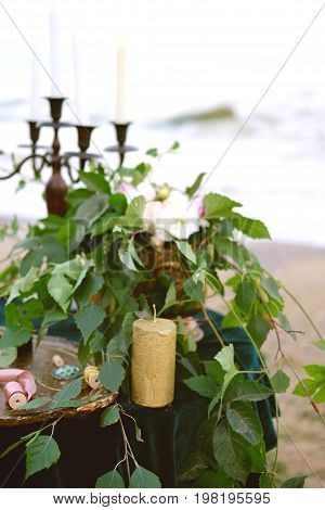 Table setting for romantic dinner on the beach with flowers candles and candle holder