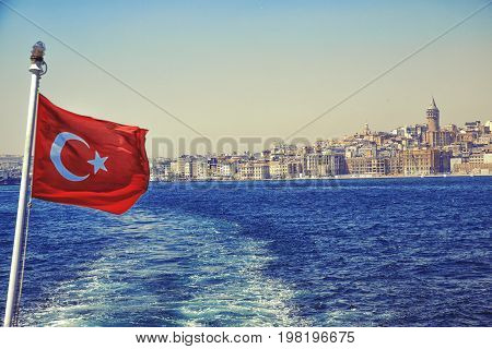 Istanbul cityscape with Galata Tower and turkish flag from the water