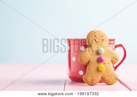 Gingerbread man leaning against a cup on pink table. Xmas gingerbread.