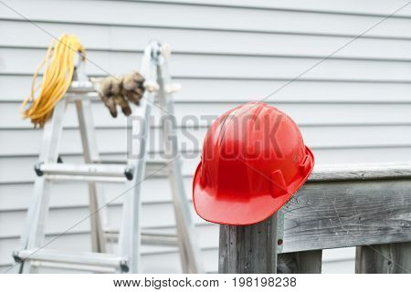 Red hardhat with ladder and exterior siding in background