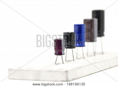 Electrolytic Capacitors multi color and many sizes on white background Electronics part concept.