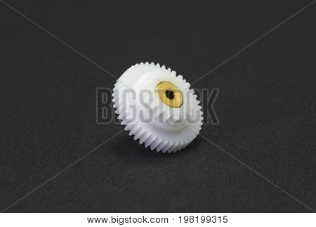 Plastic gear spare part in the fragment of machine on black background.