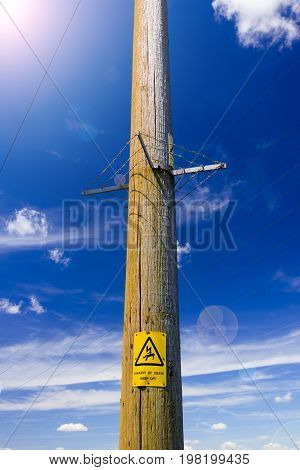 Electricity poles reach up into the deep blue sky. A warning sign warns of impending danger