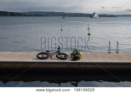 Man With Fat Bike Lying On Wood Jetty In Sunshine