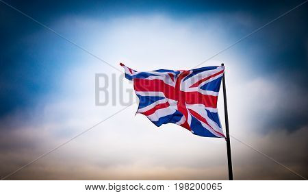 A Union Jack flag is accentuated against a dramatic sky
