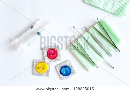 Visit the urologist. Syringes, tools and condoms on white background top view.