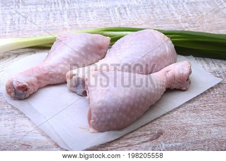 raw chicken legs with spices on a wooden board. Ready for cookin