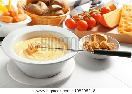 Cheese fondue in plate and different products on white table