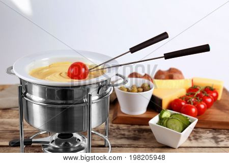 Tomato and cheese fondue in pot on kitchen table