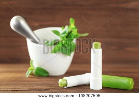Hygienic lipsticks with lemon balm on wooden table