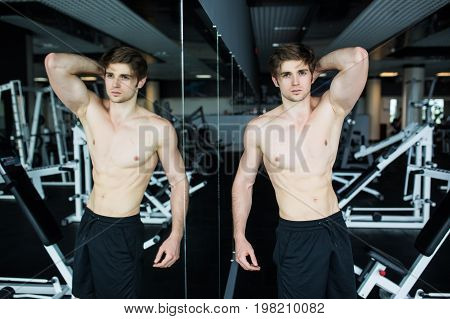 Muscular, Shirtless Young Man Resting In Gym During Workout, Showing Muscular Torso, Pecs And Abs In