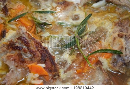 Delicious savory meat course stewed with vegetables and rosemary greenery