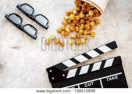 Watching film. Clapperboard, glasses and popcorn on grey stone background top view.