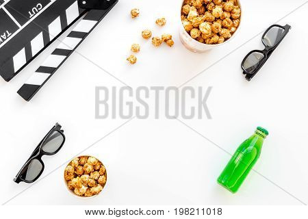 Watching film. Clapperboard, glasses and popcorn on white background top view.