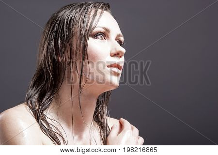 Beauty Concepts and Ideas. Portrait of Sensual Sexy Caucasian Brunette Female Looking Up with Wet and Shining Skin and Wet Hair. Against Dark Grey Background. Horizontal Image Orientation