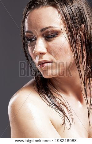 Portrait of Sensual Tanned Caucasian Brunette Woman With Sad Expression with Wet and Shining Skin and Wet Hair. Against Dark Grey Background. Vertical Image Composition