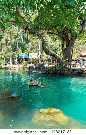 VANG VIENG LAOS - MARCH 14 2017: Vertical picture of black hair girl playing at the swing in Blue Lagoon located close to the city of Vang Vieng Laos.