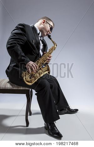 Music Concepts. Portrait of Mature Relaxed and Thoughful Caucasian Saxophone Player in Sunglasses Playing the Saxophone While Sitting on Chair in Studio Environment. Vertical Shot