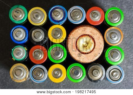 Used batteries. Horizontal shot.20 of the multicolored used electric batteries and one cartridge case from the cartridge top view
