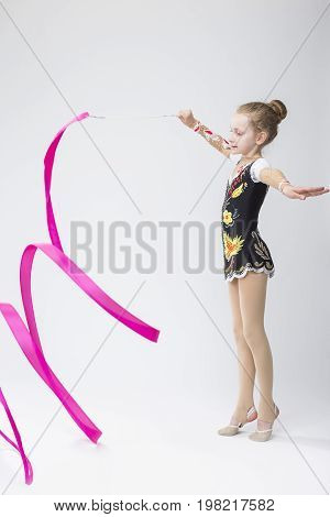 Professional Sport Concepts. Little Caucasian Female Rhythmic Gymnast In Professional Competitive Suit Doing Artistic Ribbon Spirals Exercises in Studio Against White. Vertical Image Composition