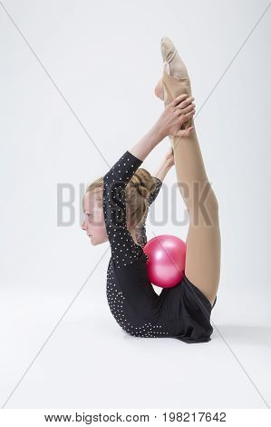 Sport Concepts. Caucasian Female Rhythmic Gymnast In Professional Competitive Black Sparkling Suit Doing Backbend Stretching Exercise With Ball in Studio On White. Vertical Image Composition