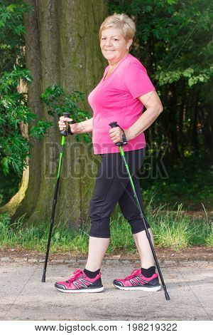 Elderly Senior Woman Practicing Nordic Walking, Concept Of Sporty Lifestyles In Old Age