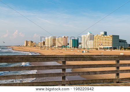 VIRGINIA BEACH, VIRGINIA - JULY 13, 2017:  The railing of the fishing pier at daybreak on the boardwalk along the oceanfront, with high-rise hotels in the background.