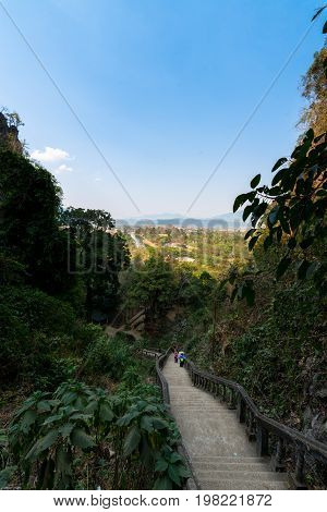 VANG VIENG LAOS - MARCH 14 2017: Vertical picture of the stairs to reach the Tham Chang Cave in the city of Vang Vieng Laos. Tropical Vegetation.