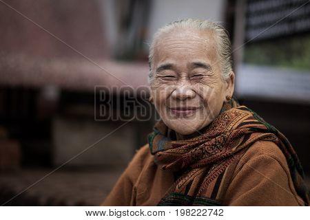 Luang Prabang, Laos - December 21, 2015: An elder of local settler is introduce herself to the tourists in Luang Prabang, Laos.