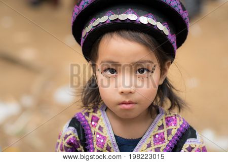 Luang Prabang, Laos - December 20, 2015: A little girl of local mountaineer tribe 'Hmong' is dressing with traditional costume in Luang Prabang, Laos.