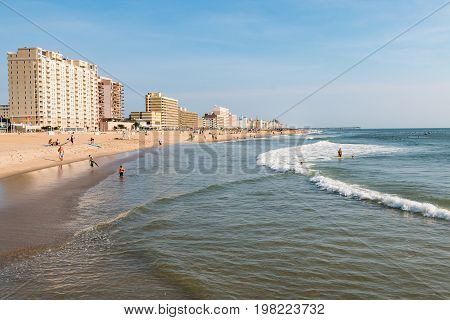 VIRGINIA BEACH, VIRGINIA - JULY 13, 2017:  People enjoy beach-front leisure activities on the south end of the 3-mile oceanfront lined with high-rise hotels.