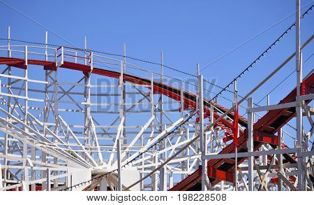 A wooden rollercoaster track against a clear blue sky