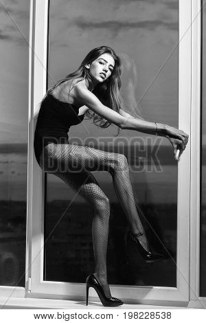 model with long hair and legs in fishnet tights shoes and lingerie stands at window on sky background black and white