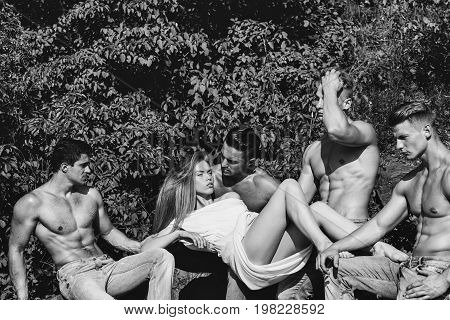 men with muscular sexy body and six packs on torso in jeans and pretty woman in dress sunny outdoor on natural background black and white