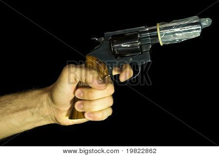 Male hand holding a revolver with a condom on it. Black background.