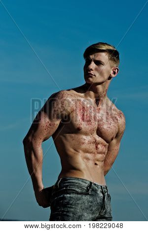 Athletic bodybuilder pose as hercules. Sport and workout. Gladiator or atlant. Man with muscular wet body. Adam with glitter on bare chest.