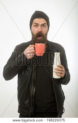 Dieting and health. Man with long beard and surprised face hold milk bottle. Food and drink. Hipster in hat with yoghurt and cup. Ecology product and glass.