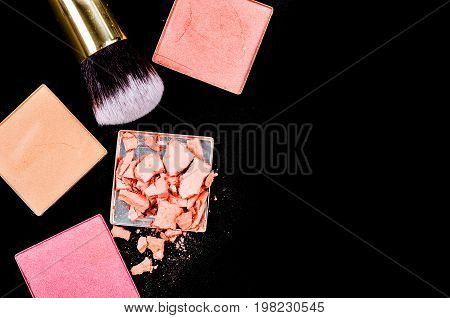 Makeup cosmetics products on dark background with copy space.