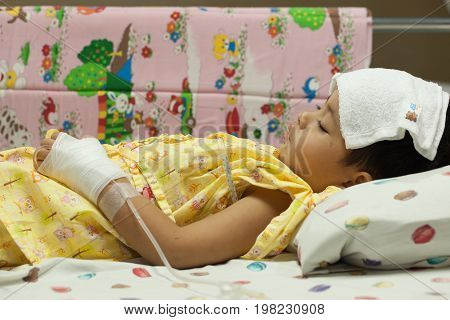 a little Boy attaching intravenous tube to patient's hand in hospital bed thermometer boy hospitalized patients towel to high fever