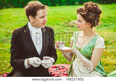 Beautiful girl in the lush dress drinks tea. Photoshoot in the Rococo style. Historical Portrait.