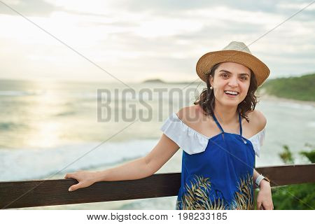 Happy laughing young woman on sunset light ocean background