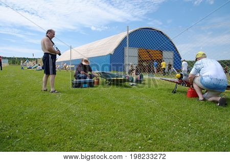 PENZA OBLAST, RUSSIA - JULY 15, 2017: A man fueling radio control flying model of Supermarine Spitfire aircraft. The Russian Aeromodelling Cup in Bolshoy Vyas village.