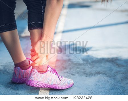 Young woman suffering from an ankle injury while exercising and running. Sport exercise injuries concept.